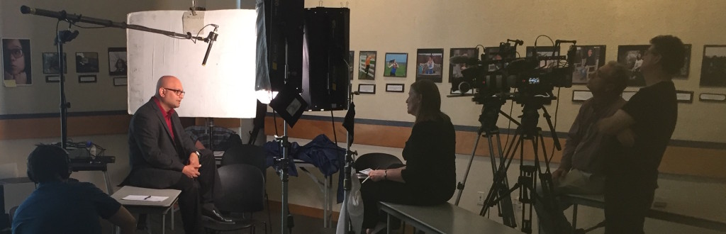 A photo of Associate Professor Amit Savkar being interviewed on camera in his classroom.